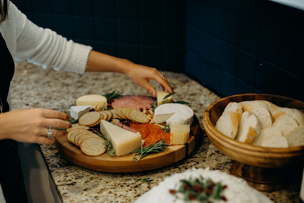 Hands setting up a charcuterie board in a kitchen with bread and cake on the counter