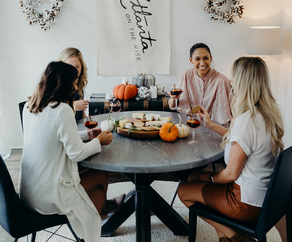 Girls Gathering Around a Table with Pumpkins and a charcuterie board