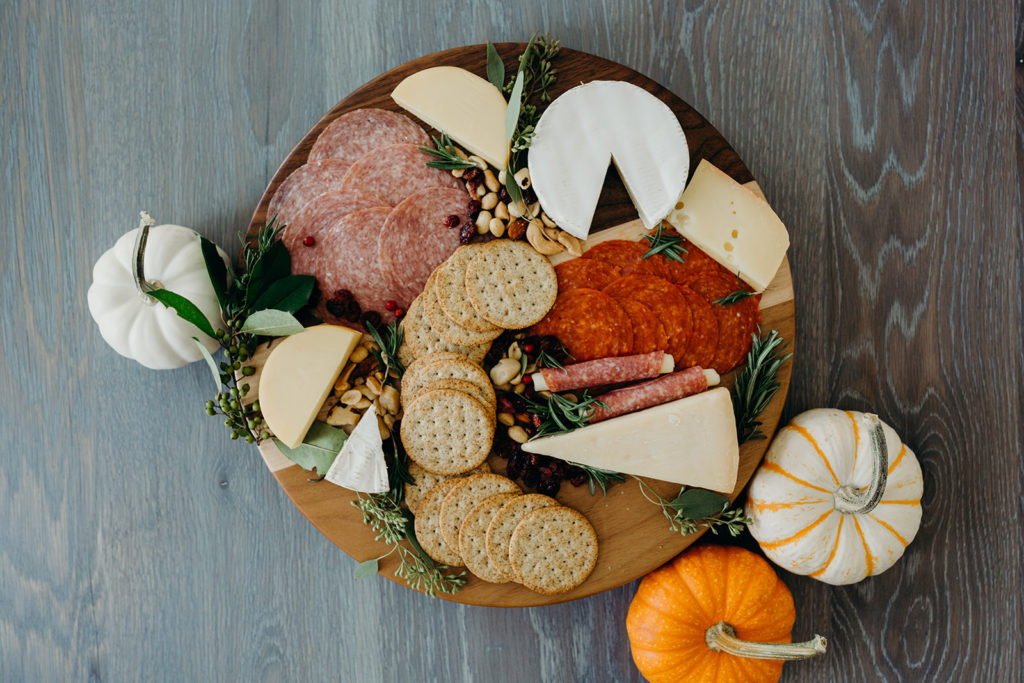 charcuterie board with pumpkins on a table top
